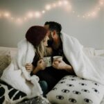 Couple snuggling with blankets and coffee mugs