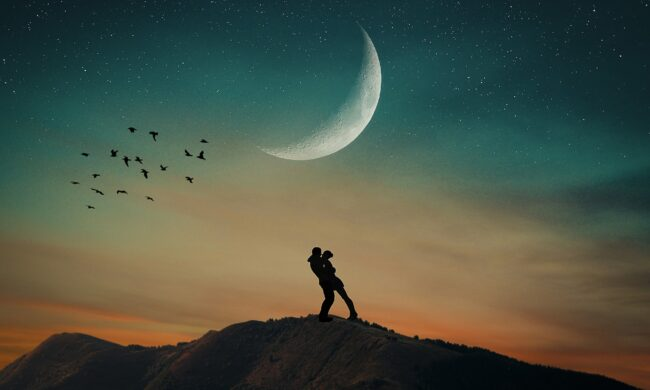 Couple embracing on mountain under crescent moon