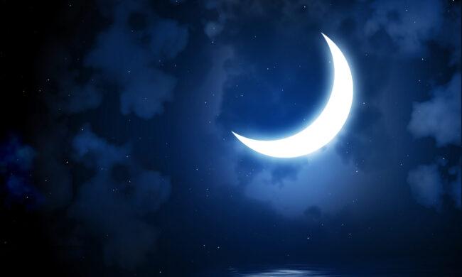 Bright crescent moon over ocean